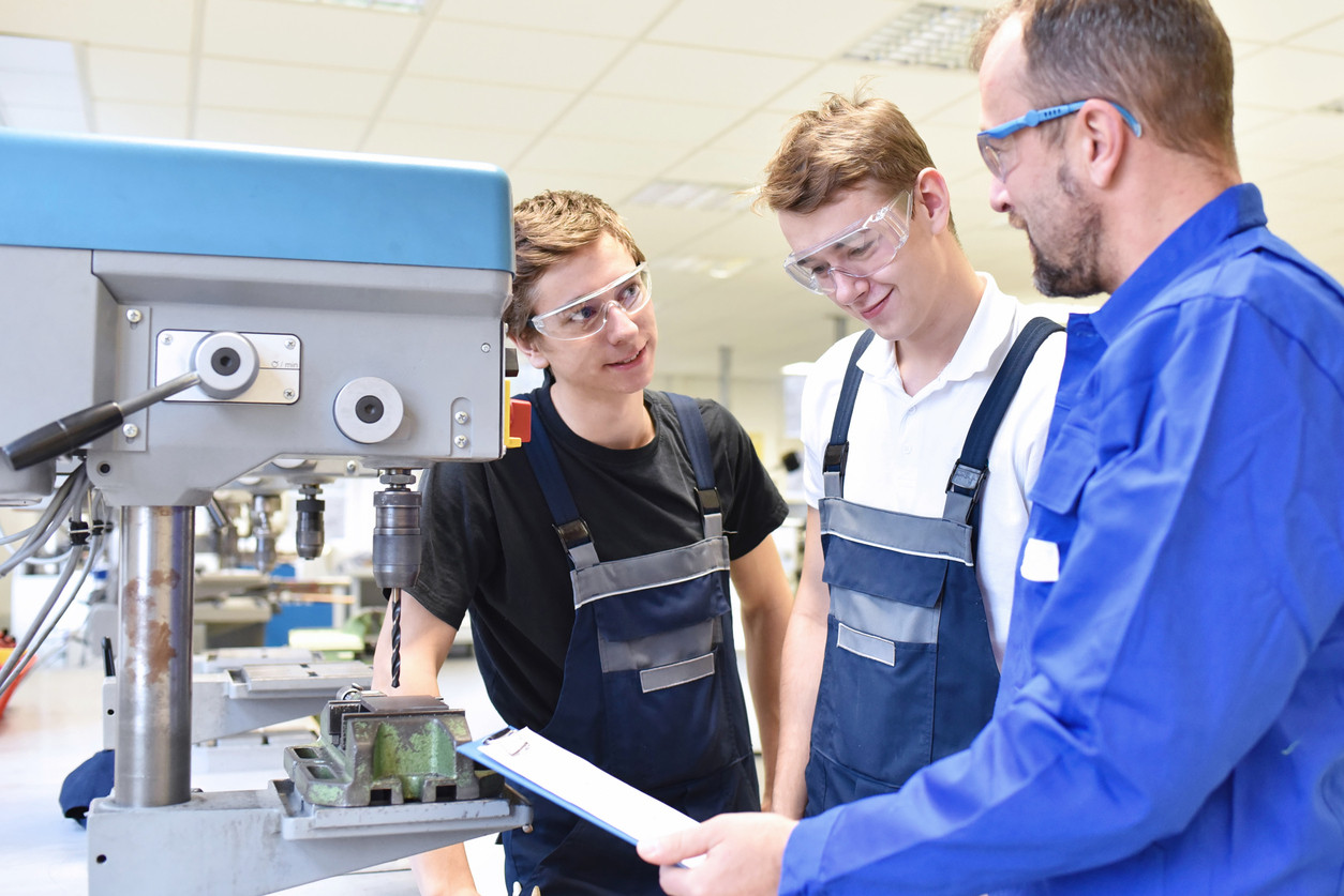 trainer and apprentice in technical vocational training at a drilling machine